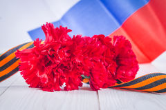 Carnation and ribbon of St. George, as a symbol of victory against the background of the Russian flag. May 9, the day of victory. Stock Photo
