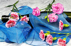 Carnations with a bottle and a blue scarf Stock Images
