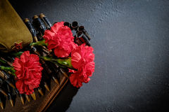 Carnations with forage-cap and ammunition belt on dark backgroun Royalty Free Stock Images