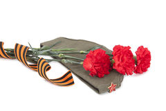 Carnations, George ribbon and field cap Stock Photography