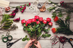 Carnations, red roses, purple callas on a wooden table in a flower shop Royalty Free Stock Photos