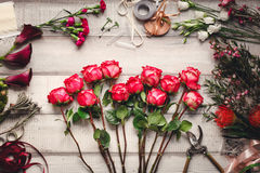 Carnations, red roses, purple callas on a wooden table in a flower shop Royalty Free Stock Image