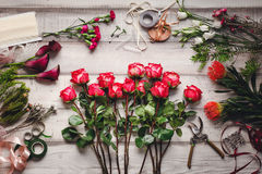 Carnations, red roses, purple callas on a wooden table in a flower shop Stock Photo