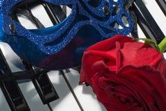 carnaval面具、钢琴钥匙和红色玫瑰的构成 图库摄影