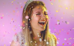 Carnaval Brazil. Throwing confetti. Face of young woman with colorful makeup, dressed up for fun. Bright background. Party concept stock image