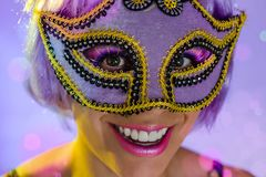 Carnaval Brazil. Portrait of latin girl with violet wig and make up mask. Color background. Masquerade concept, celebration and. Carnaval Brazil. Happiness and royalty free stock image