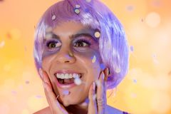 Carnaval Brazil. Portrait of latin woman wearing purple wig and makeup mask. Color background. Masquerade concept, celebration and. Carnaval Brazil. Surprised stock photography
