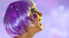 Carnaval Brazil. Portrait of latin girl with violet wig and make up mask. Color background. Masquerade concept, celebration and. Carnaval Brazil. Surprised and royalty free stock photo
