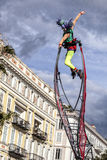Carnaval de Nice, bataille de ` de fleurs Une femme d'acrobate avec le costume de clown sur le fond de ciel Photographie stock