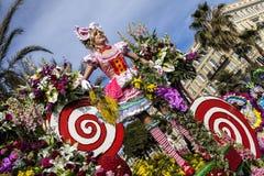 Carnaval famoso de Niza, batalla del ` de las flores Flotador grande por completo de flores coloreadas y de muchachas divertidas Imagen de archivo libre de regalías