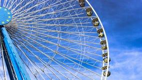 Carnaval Ferris Wheel com o SkiesClose limpo acima do tiro da metade de uma roda de ferris imagem de stock royalty free