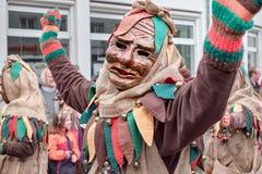 Carnaval-het cijfer in een bruin kostuum is gelukkig stock fotografie
