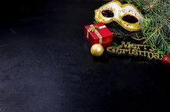 Carnaval mask and Merry Christmas inscription, fir and lights on. Carnaval mask, Merry Christmas gold inscription, fir branhes and newyear lights on black stock photography