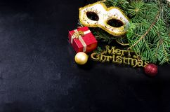 Carnaval mask and Merry Christmas inscription, fir and lights on. Carnaval mask, Merry Christmas gold inscription, fir branhes and newyear lights on black royalty free stock photography