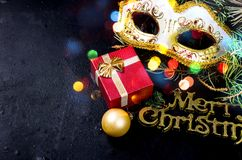 Carnaval mask and Merry Christmas inscription, fir and lights on. Carnaval mask, Merry Christmas gold inscription, fir branhes and newyear lights on black royalty free stock photos