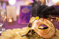 Carnaval table with venetian mask on the plate. Party. Close up. Golden mask royalty free stock photography
