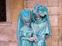 Carnaval: twee maskers in turkooise kostuums, die handen houden Stock Afbeeldingen