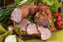 Carne ahumada del cerdo con los tomates y la ensalada Foto de archivo libre de regalías