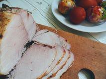 carne al forno ed uova di Pasqua su una base di legno Fotografia Stock