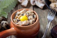 Carne al forno in un vaso con i funghi e la salsa di panna acida fotografia stock