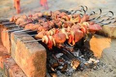 A carne amarrada em espetos é fritada sobre um fogo aberto Assado em carvões ardentes, em um feriado fotos de stock royalty free