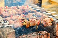 A carne amarrada em espetos é fritada sobre um fogo aberto Assado em carvões ardentes, em um feriado fotografia de stock