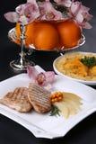 Carne arrostita calda e saporita sul piatto bianco, decorato con le arance, orchidee Immagini Stock