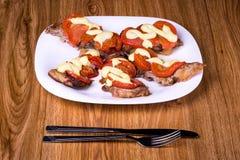 Carne arrostita con i pomodori e la maionese sul piatto su una tavola di legno Fotografia Stock Libera da Diritti