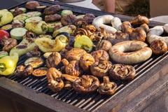 Carne arrostita deliziosa assortita con la verdura sopra i carboni su un barbecue Immagini Stock