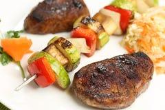 Carne arrostita e spiedi sul piatto Fotografia Stock