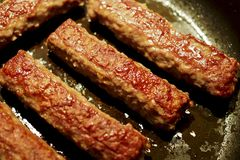 Carne arrostita in una pentola con il chevapchichi del bacon Foto con effetto del bokeh immagine stock