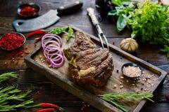 Carne asada con las cebollas, el ajo, las especias, las hierbas frescas, la pimienta roja y la sal Imágenes de archivo libres de regalías