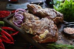 Carne asada con las cebollas, el ajo, las especias, las hierbas frescas, la pimienta roja y la sal Fotografía de archivo