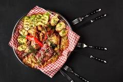 Carne asada a la parrilla deliciosa clasificada con las verduras y la salsa del Bbq en una bandeja del hierro en cierre negro del imagen de archivo libre de regalías