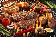 Carne asada a la parrilla deliciosa con las verduras que chisporrotean sobre los carbones en barbacoa imagenes de archivo