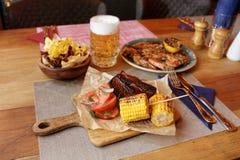 Carne asada a la parrilla, patatas del maíz, fritas y cerveza Fotografía de archivo