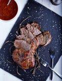 Carne assada na placa de pedra preta com molho Fotos de Stock