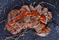 Carne assada na placa de pedra preta com molho Fotos de Stock Royalty Free