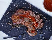 Carne assada na placa de pedra preta com molho Imagem de Stock Royalty Free