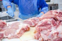 Carne che disossa negozio macellaio I macellai stanno tagliando la carne di maiale Linea di fotografia stock libera da diritti