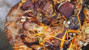 Carne che frigge nel fuoco di accampamento closeup stock footage