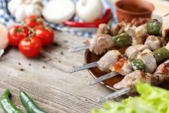 Carne cocinada en un fuego abierto Kebabs en los pinchos presentados en una placa Aún-vida en un fondo de madera Primer Fotos de archivo libres de regalías