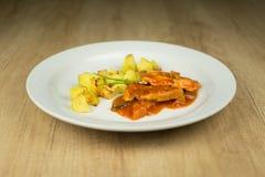 Carne com as batatas fervidas na placa na tabela de madeira Fotografia de Stock