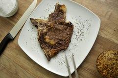 A carne com forquilha de cinzeladura e a faca do cozinheiro chefe dobram Fotos de Stock