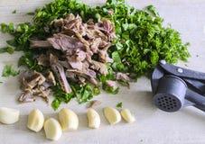 Carne com os cravos-da-índia de alho inteiros e de ervas frescas em uma boa de madeira Imagem de Stock Royalty Free