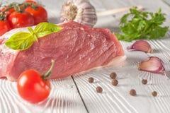 Carne com tomates e verdes em um fundo de madeira branco Fotos de Stock Royalty Free