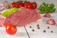 Carne com tomates e verdes em um fundo de madeira branco Foto de Stock