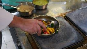 A carne com vegetais em um cozinheiro chefe da frigideira impede e joga a carne com vegetais em uma frigideira, cozinhando o ragu vídeos de arquivo