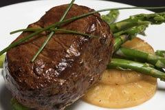 Carne con asparago e l'ananas sul piatto bianco e sul fondo nero immagine stock