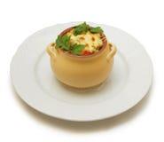 Carne con el huevo soft-boiled y verdes en el crisol Fotos de archivo